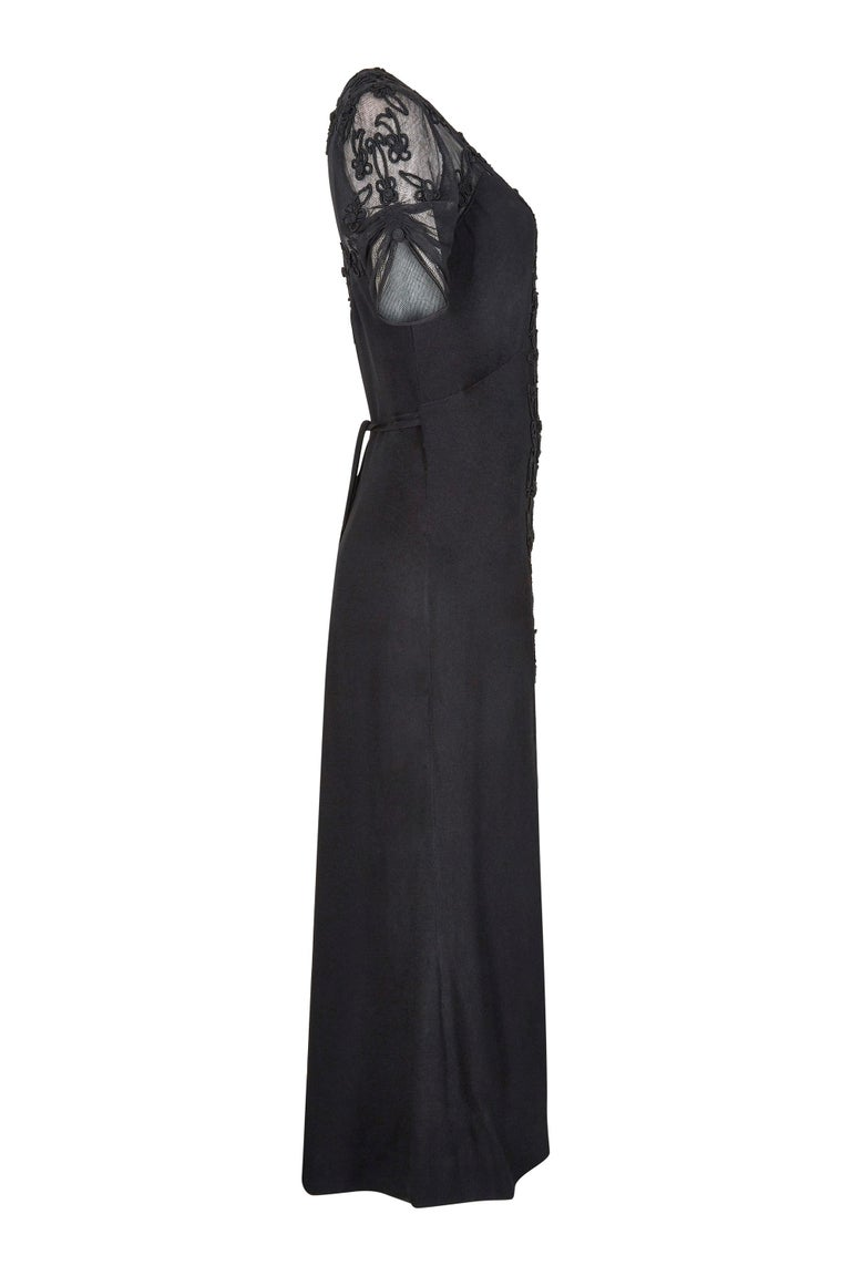 This incredible 1930s black silk crepe evening dress with soft net bodice is in fantastic vintage condition with some beautiful design features. The dress has a plunging scoop neckline and sheer net fabric on the shoulders and upper back. The soft