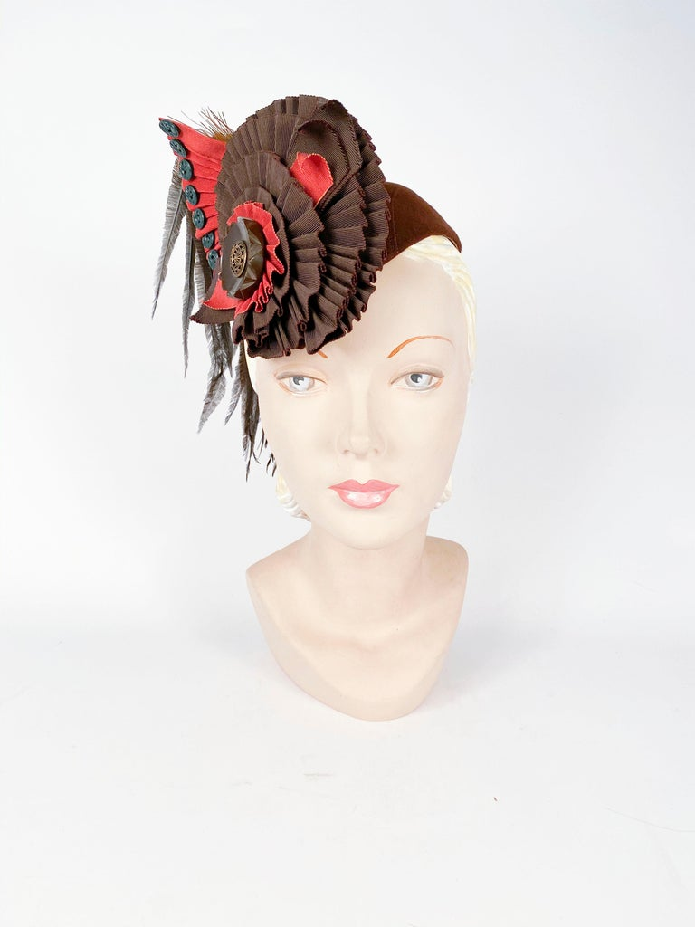 1930s Brown beaver fur felt hat with rust-colored and chocolate brown structured ruffled ribbon accent centered with a large bakelite button finished with hand-curled feathers.