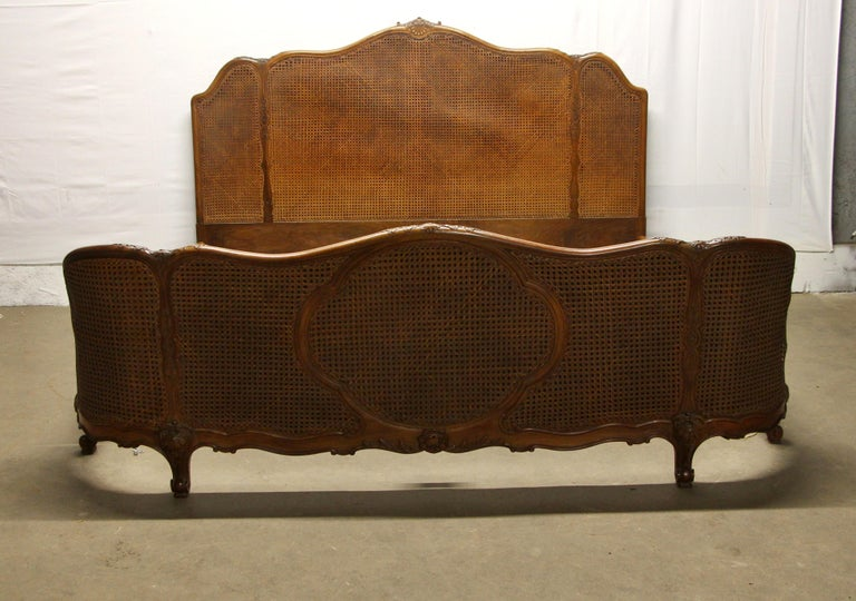 1930s dark wood tone king size Art Deco bed done in walnut with cane and carved wood details. There is general wear from age and use, and some damage to the caning and frame. Please see photos. This can be seen at our 400 Gilligan St location in