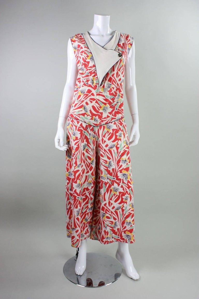Vintage beach pajamas date to the late 1920's through mid-1930's and are made of a soft red cotton with a stylized Art Deco floral print.  V-neck has a textured white cotton center front panel.  Single silver-toned button on white panel.  Garment is