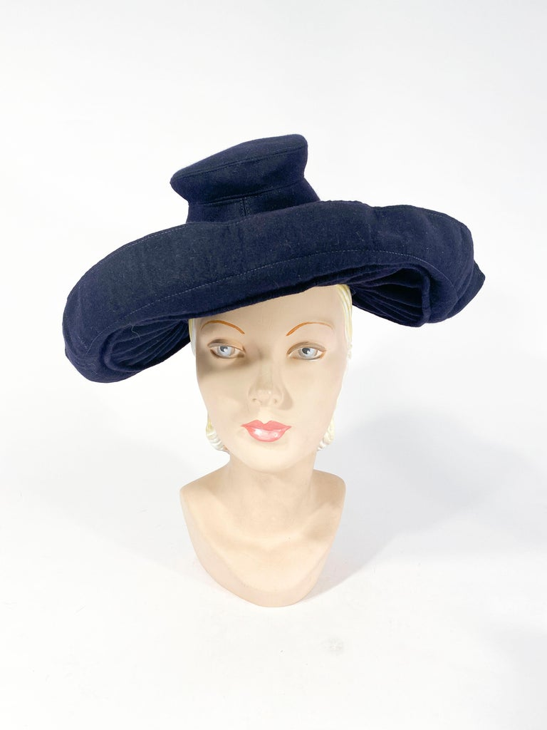 1930s Dark navy blue hat with a gathered wide brim that folds back at the edge lined with red contrasting gros-grain ribbon. The crown of this hat is hand-sculpted in a silhouette made famous by Adrian during the 1930s.