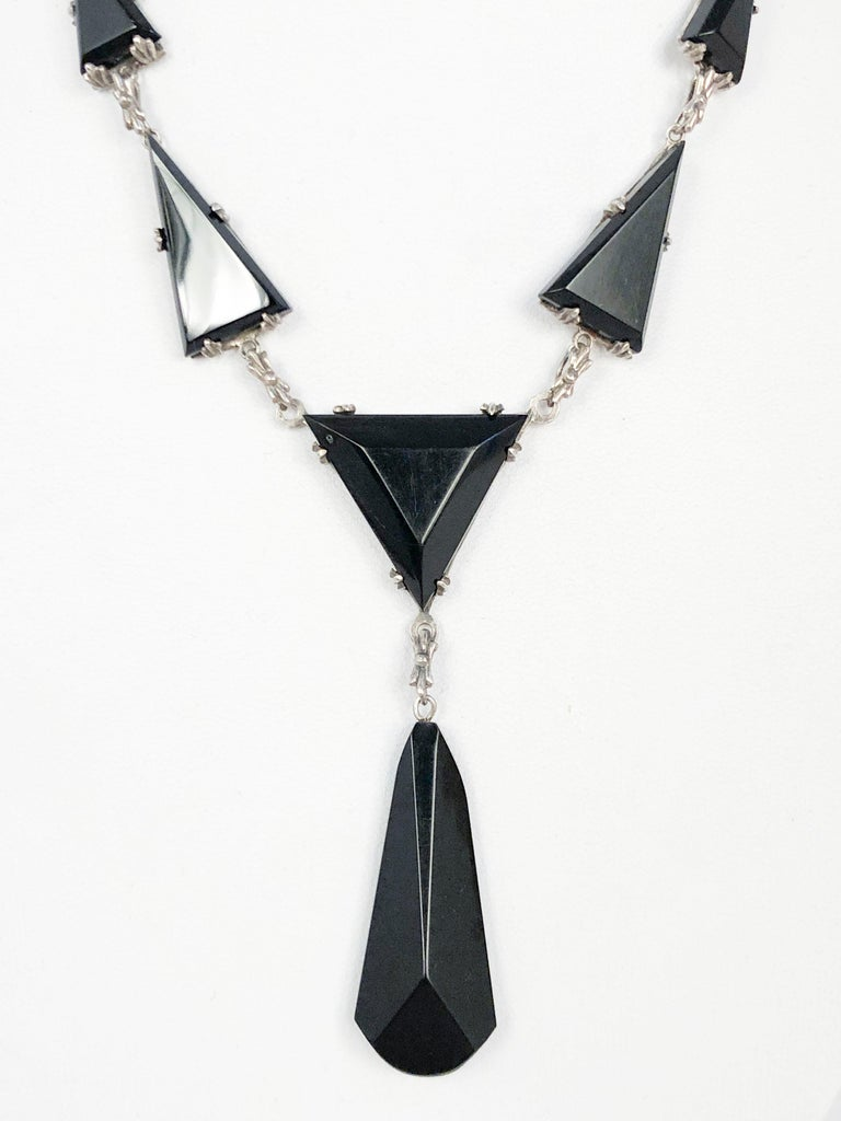 1930s Art Deco Silver necklace featuring geometric shaped onyx and black bakelite, teardrop hanging accent and filigree closure.