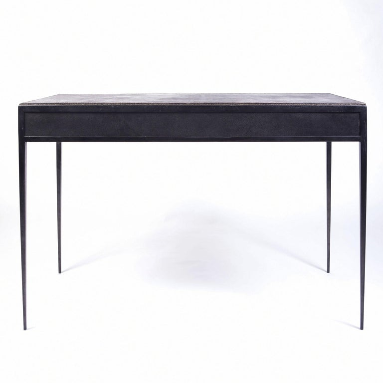 A desk of exceptional quality, demonstrating exactly the designer's mastery of perfectly balanced minimalist lines, with their tapered legs and precise detailing. Iron legs support the black/grey leather top with two cerejeira (Brazilian oak)