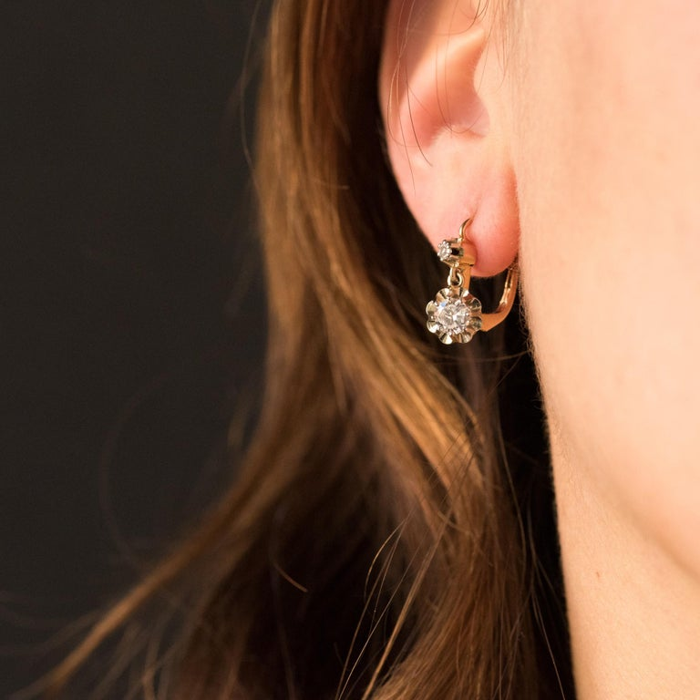 Earrings in 18 karats rose and white gold, eagle's head hallmark. Antique drop earring, each is set with claws of a brilliant-cut diamond on a sun set surmounted by a smaller diamond. The closure system is from the front. Total weight of diamonds: