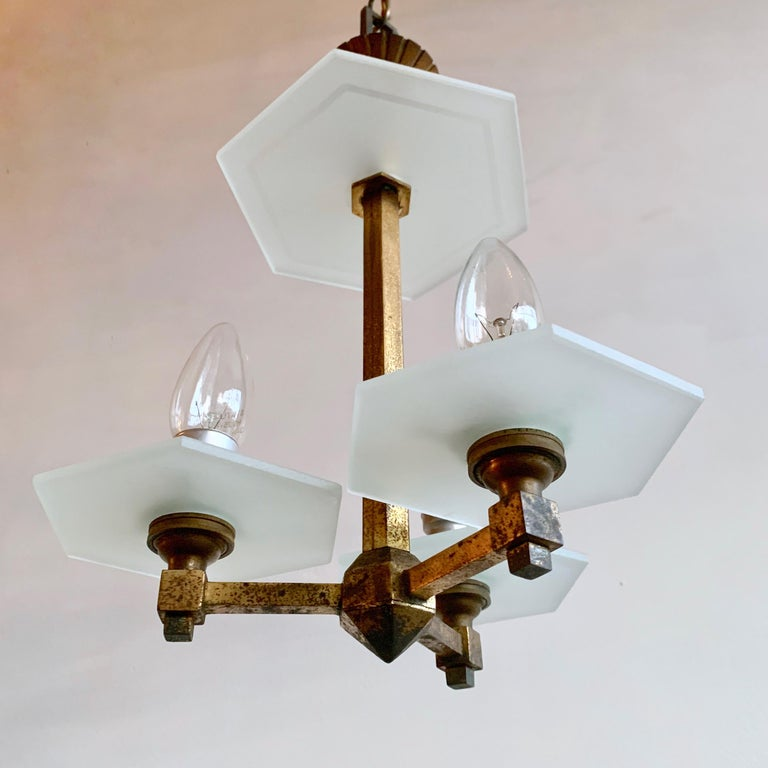 Petite 1930s Art Deco brass chandelier with hexagonal frosted glass pieces. This chandelier has three lamps. This piece was originally gilt that has aged leaving an off-black and gold patina. It has elegant proportions and would suit a hall way or