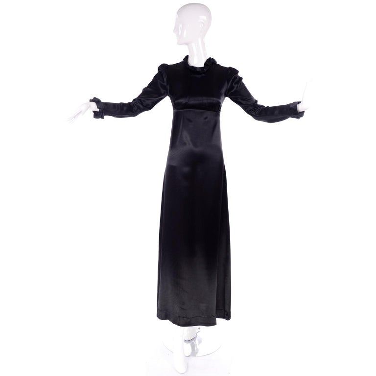 This is an amazing 1930's vintage black dress that in a Victorian style. This lovely dress has a ruffled neckline and ruffled cuffs on the long sleeves. It is a silk satin fabric, and there are unique seams on the bodice that creating a fitted