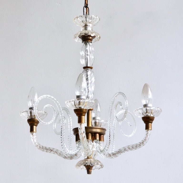 A four branch French glass chandelier dating from the 1930s. A beautifully proportioned chandelier with elegant details. The angle of the arms are unusual and are slightly elongated. There are four walking sticks with scrolling glass swirls in