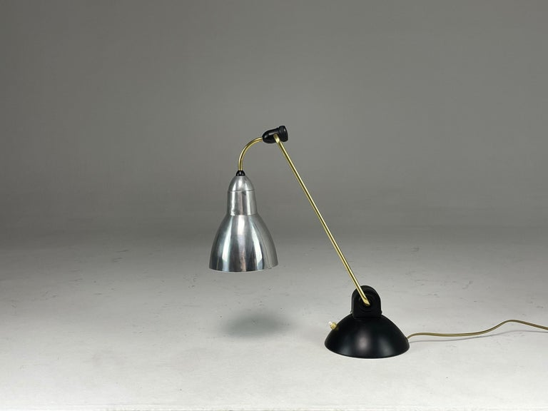 A striking French 20-century vintage desk or table lamp composed of aluminum, steel and brass. The base features a push-type switch and the light rotated and the base and shade.  The base was restored with new black lacquer.  Professionally