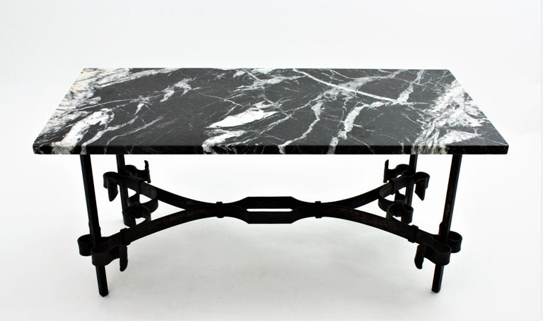 Elegant patinated wrought iron rectangular low table with black and white marble top. In the style of Gilbert Poillerat. France, 1930s. The four-footed iron base has a stretcher to join the legs, scroll details and a beautiful aged patina still