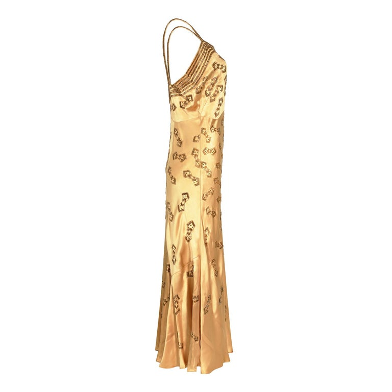 A very eye catching original Art Deco beaded and sequinned dress in extraordinary condition for its age. The exquisite angled 'bow tie' design is repeated all over the dress and the rich embellishment complementary against the warm gold coloured