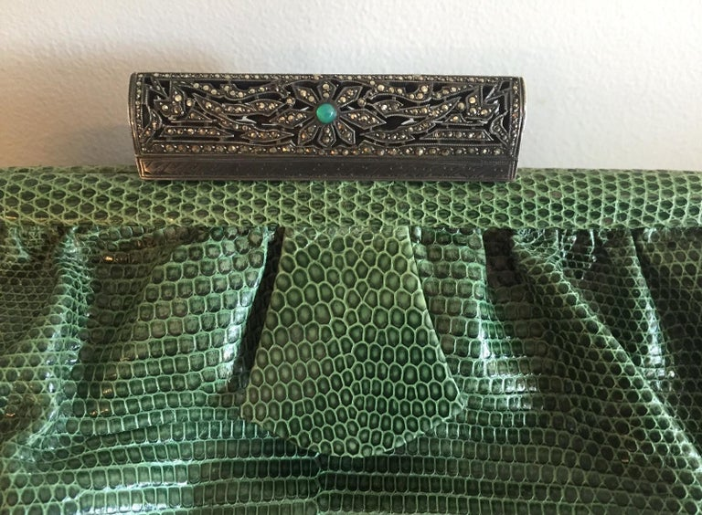 This 1930's Art Deco lizard clutch bag will add a pop of color to any outfit. It has a silver clasp [unmarked so I can't say that it is sterling but that would be my guess] studded with marcasite and a chrysoprase cabochon at the center. This is