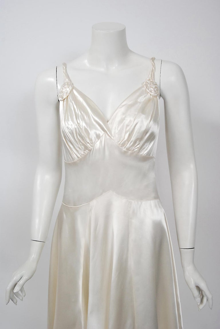 An elegant 1930's custom made ivory silk-satin slip dress from the Old Hollywood era of glamour. The bodice has a seductive low-cut sculpted plunge with detailed rosette appliques. The thin braided straps and back covered buttons add the perfect