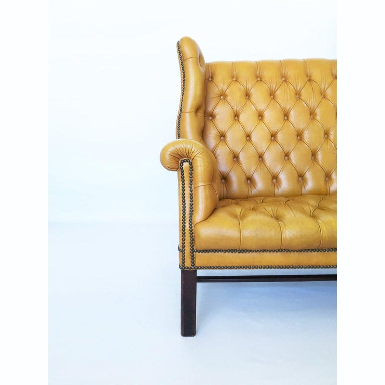 This handsome George III style wing back tufted leather settee is the definition of old fashioned luxury. Featuring a warm mustard leather tufting with out-scrolled wings & arms all resting on square Marlboro front legs & splayed back legs that are