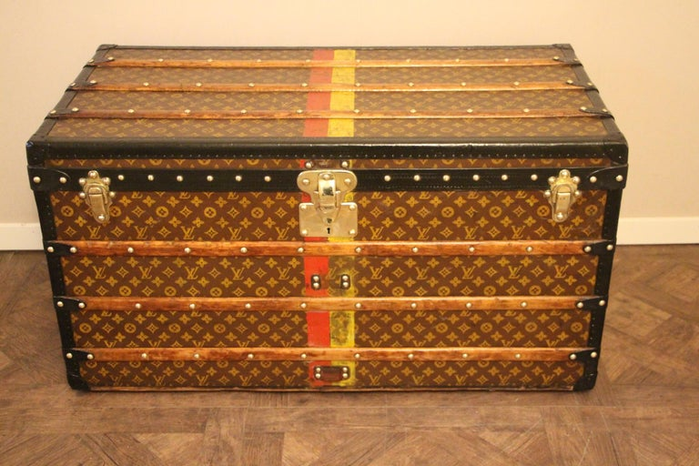 This Louis Vuitton trunk features stenciled canvas, deep black lozenge trim, black steel side handles, solid brass Louis Vuitton stamped brass lock and clasps as well as Louis Vuitton stamped brass studs. Yellow and red customized painted stripes.