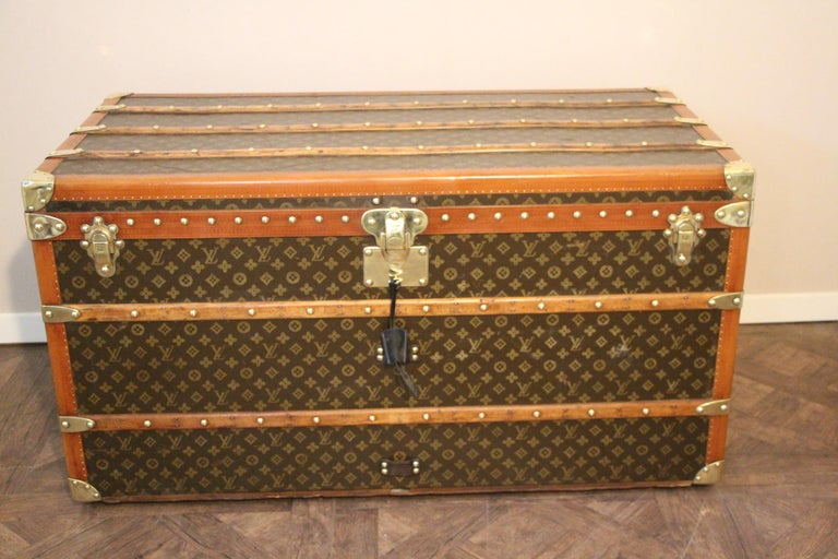 Beautiful Louis Vuitton steamer trunk featuring stenciled canvas, all honey color lozine trim, solid brass Louis Vuitton stamped clasps and lock, solid brass corners and large leather side handles.