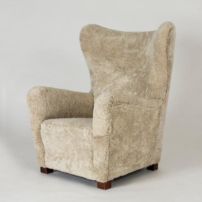 Elegant 1930s lounge chair from Fritz Hansen, with clean, stately lines. Upholstered with sheepskin that softens the silhouette.