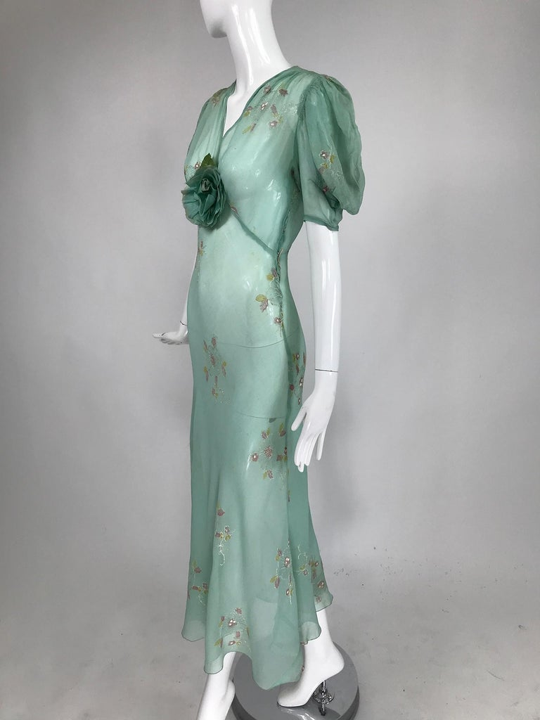 1930s mint green, hand embroidered, bias cut sheer silk chiffon maxi dress. This amazing vintage 30s dress is so evocative of the period. V neck dress has elbow length puff sleeves, the dress has a matching green rose corsage at the bust