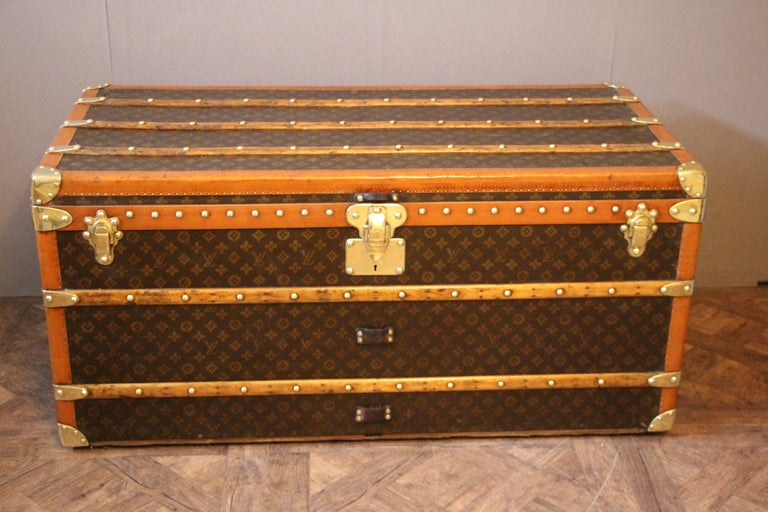 This beautiful Louis Vuitton trunk is all stenciled LV monogram canvas, with all Louis Vuitton stamped brass hardware and lozine trim. It features large leather side handles as well as a customized French flag on each side. It has got a very warm