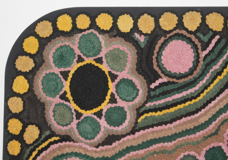This amazing hand hooked mounted colorful rug has a custom made mount with rounded corners. The condition is very good with minor wear in the center of the rug. The condition otherwise is fantastic.