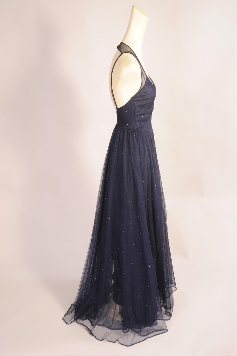 Like twinkling stars in the night sky, rhinestones glisten on this beautiful 1930's cotton net dress. It has a halter style neckline with narrow straps at the back. The fitted bodice has a left side metal zipper and the skirt is two layers of tulle.