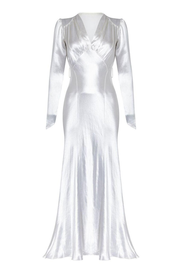 This enchanting 1930s silk satin wedding gown is in really good vintage condition and of exceptional quality. The opulent silvery white satin fabric is unlined and expertly tailored to create a flattering fairytale silhouette that would complement a
