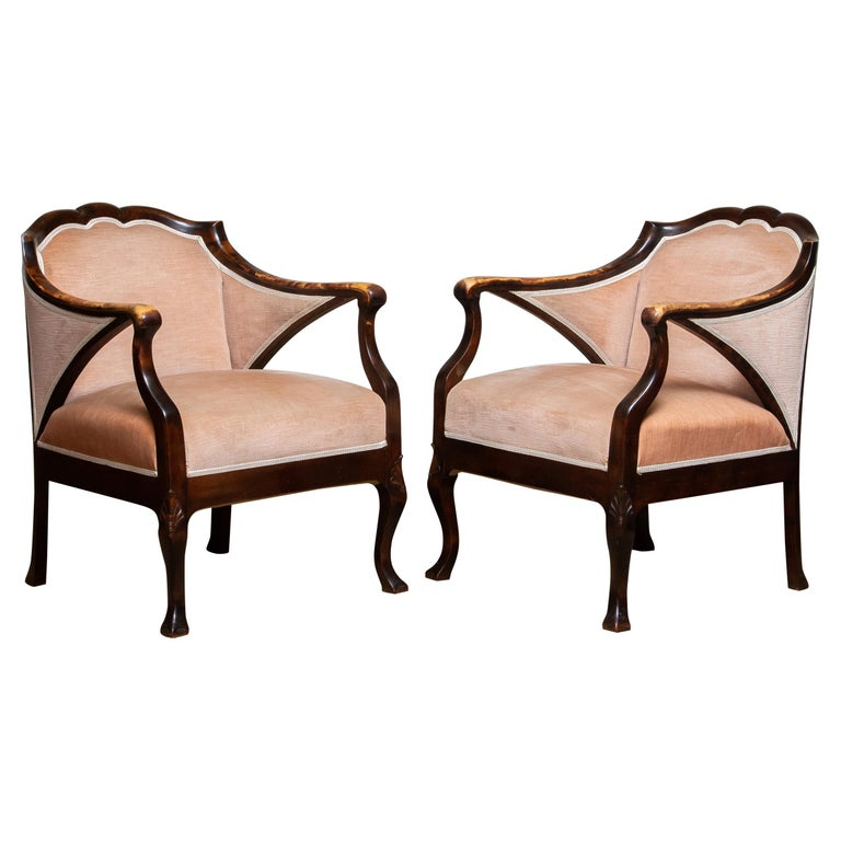 Beautiful set of two Art Nouveau easy / armchairs in beech upholstered with Salmon color velvet after Fritz Hennings from the 1930's. What makes the chairs particularly beautiful is the discoloration on the armrests over the years. Both chairs are