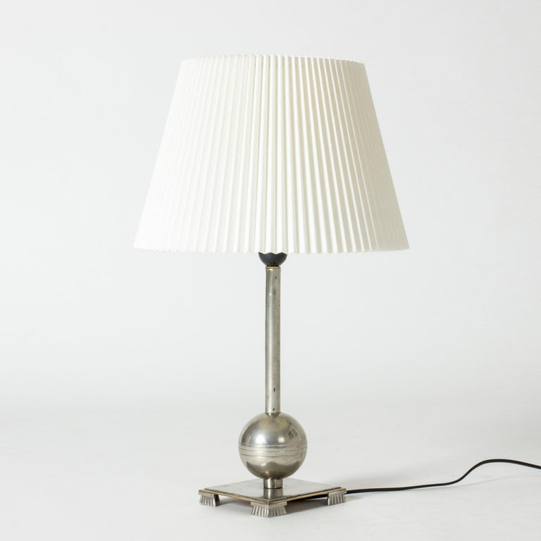 Elegant pewter table lamp by Einar Bäckström, in a functionalist design with a square base with decorative feet, and a globe on the handle.