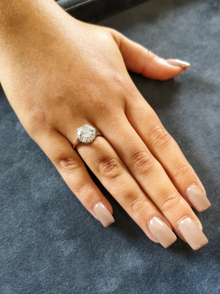 The fine, bright and lively 'transition' brilliant cut diamond mounted in a traditional basket setting with six double claws. Approximately 3.29 carats, G colour SI2 clarity. Uniform, polished, squared 18-carat white gold shank, stamped 18ct Plat.