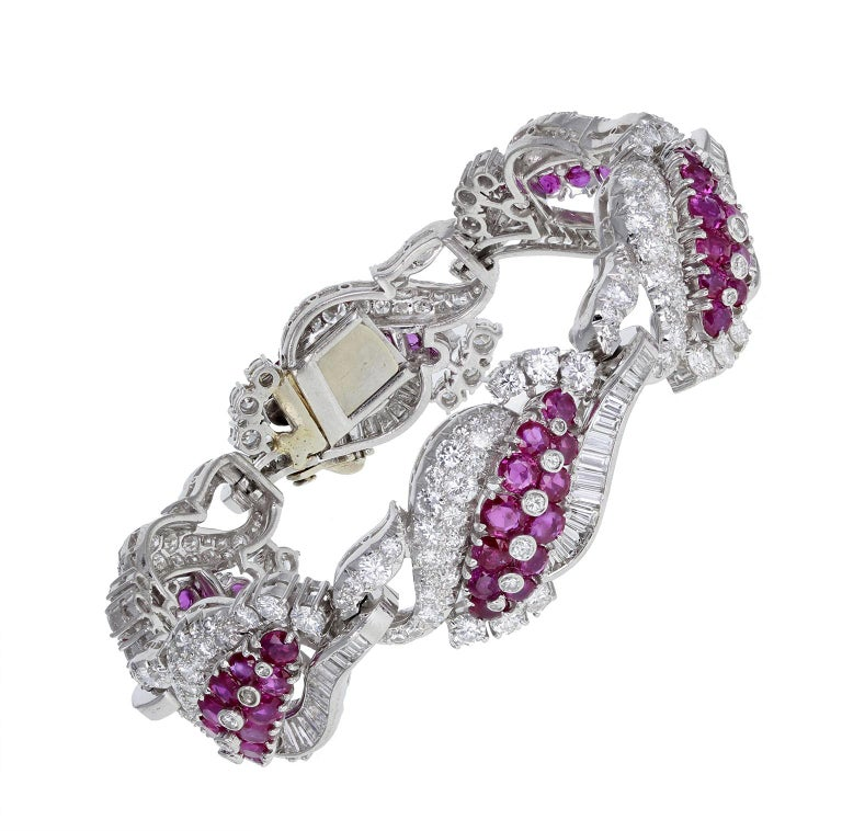 An exquisite 1930s diamond and Burma ruby bracelet in platinum. Comprising curved, pierced sections, mounted with claw-set, brilliant-cut blood-red Burma rubies and brilliant and baguette-cut diamonds. 18-carat white gold clasp. A particularly fine