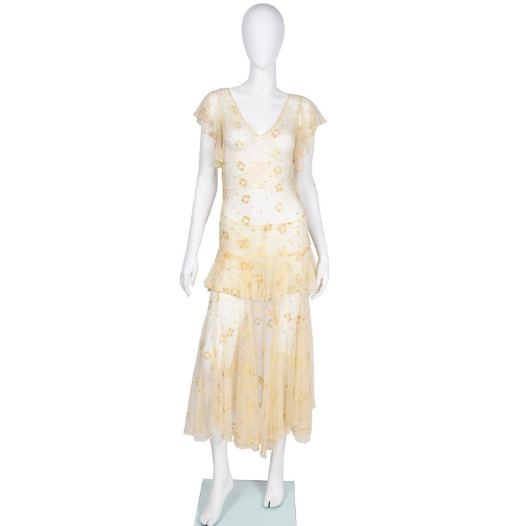 This dress is so incredible! It is made of a sheer creamy beige rayon or silk net with pastel embroidered flowers throughout dress. The  embroidery is various shades of pink, yellow, and gree and the dress has butterfly sleeves, a. V-neck and ribbed