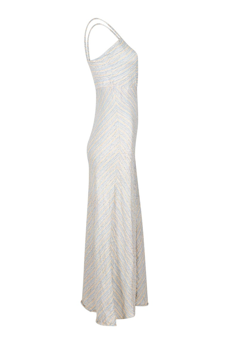 This enchanting 1930s floor sweeping bias cut silver lamé gown with matching cropped jacket is in beautiful vintage condition with exquisite finishings although unlabeled. The soft ivory and pale blue striped silk fabric is arranged alongside the