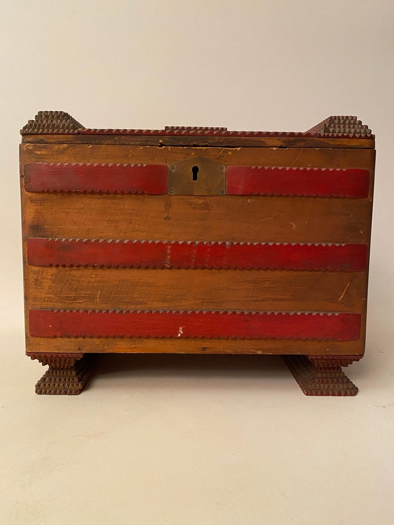 Tramp art box, circa 1920-1930, made of Victor cigar boxes and scraps of wood. Each decorative tiered layer and feet is notch carved. Wonderful two tone contrast of red and the warm brown tones of the natural wood boxes. The lock had been taken out.