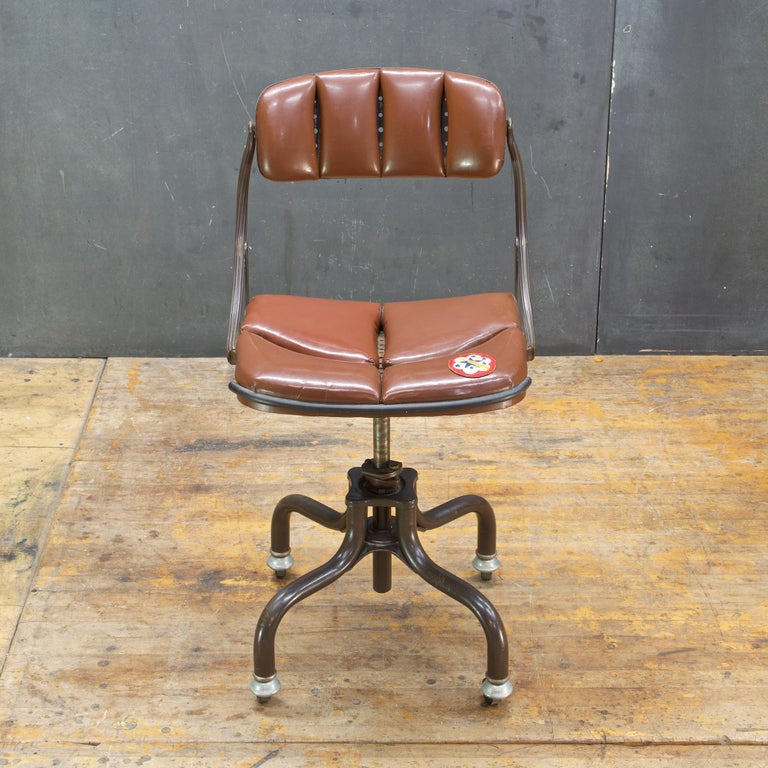 Vinyl Color is a Burnt Sienna (a darker verison, a brown with rust.) Intact original segmented vinyl upholstery, with some cracking of vinyl. Presented in as-found unrestored condition with an old repair with a WWII Army Western Pacific