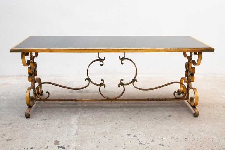 Beautifully Art Deco coffee or centre table with a wrought iron base and the warm original gilded and black smoked detailing of the glass top, detailed design of pleasant curves, very nice example of French, 1930s Art Deco