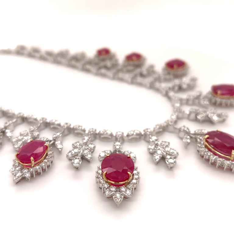 Royal ruby diamond necklace earrings set. High brilliance, oval faceted, 19.32 carats natural rubies mounted in an open basket profile with yellow gold prongs, accented with round brilliant cut diamonds, in dangling drops. Handcrafted breathtaking