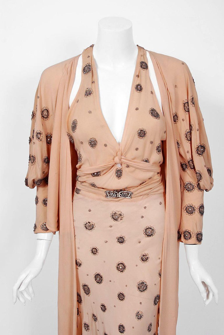 A breathtaking blush-peach silk gown and jacket set worn by Tallulah Bankhead in the 1932 Paramount film 'Devil and the Deep'. Bankhead wore this ensemble for the first thirty minutes of this film. The halter t-style gown is embellished with
