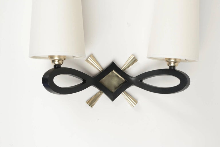 1940 pair of wall lights by Marcel Guillemard.  Each sconce consists in a large black lacquered bronze knot highlighted with a gilded bronze diamond-shaped plate and cross.  Two lighted arms and two white ivory cotton lampshades.  The