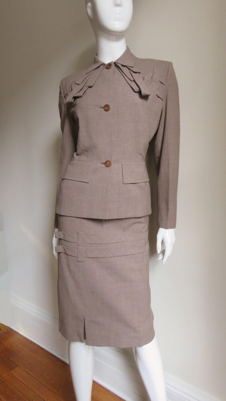 A fabulous suit from the legendary Gilbert Adrian known for impeccable designs and tailoring for film and the famous.  There is an amazing attention to detail in this 2 piece tan light weight woven wool skirt suit.  The jacket has shoulder pads, a