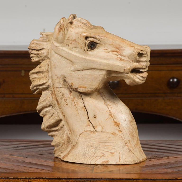 An American carved wooden horse head fragment from the mid-20th century, with nicely weathered patina. Made in America during the second quarter of the 20th century, this carved wooden head captures our attention with its expressive features and