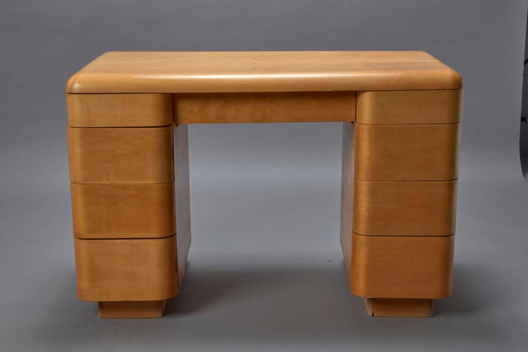 This Art Deco-style bentwood Mid-Century Modern writing desk was designed by Paul Goldman in 1946 for Plymold Co. This desk has eight drawers and one central long drawer that are flushed into the frame when closed.