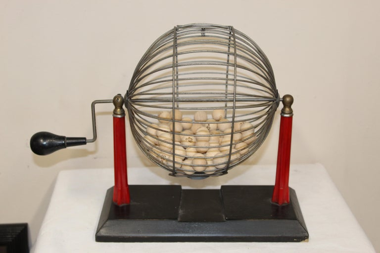 Bingo cage with bakelite red stand and an handle. Original condition, some small imperfections but over all in clean condition. Wood balls are included and numbered.