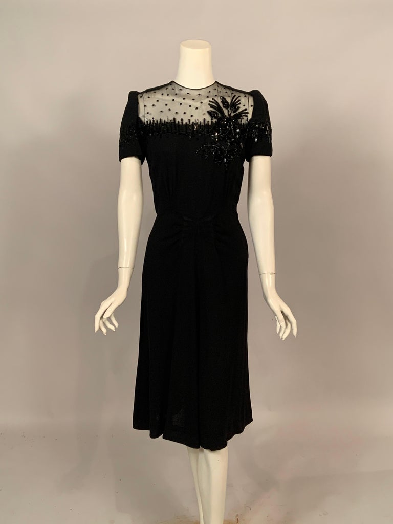 A truly glamorous black crepe dress with a sheer panel embellished with scattered sequins, vertical rows of  black sequins on the sleeves and bustline and a beautiful three dimensional floral corsage on the left side. The dress has three vertical