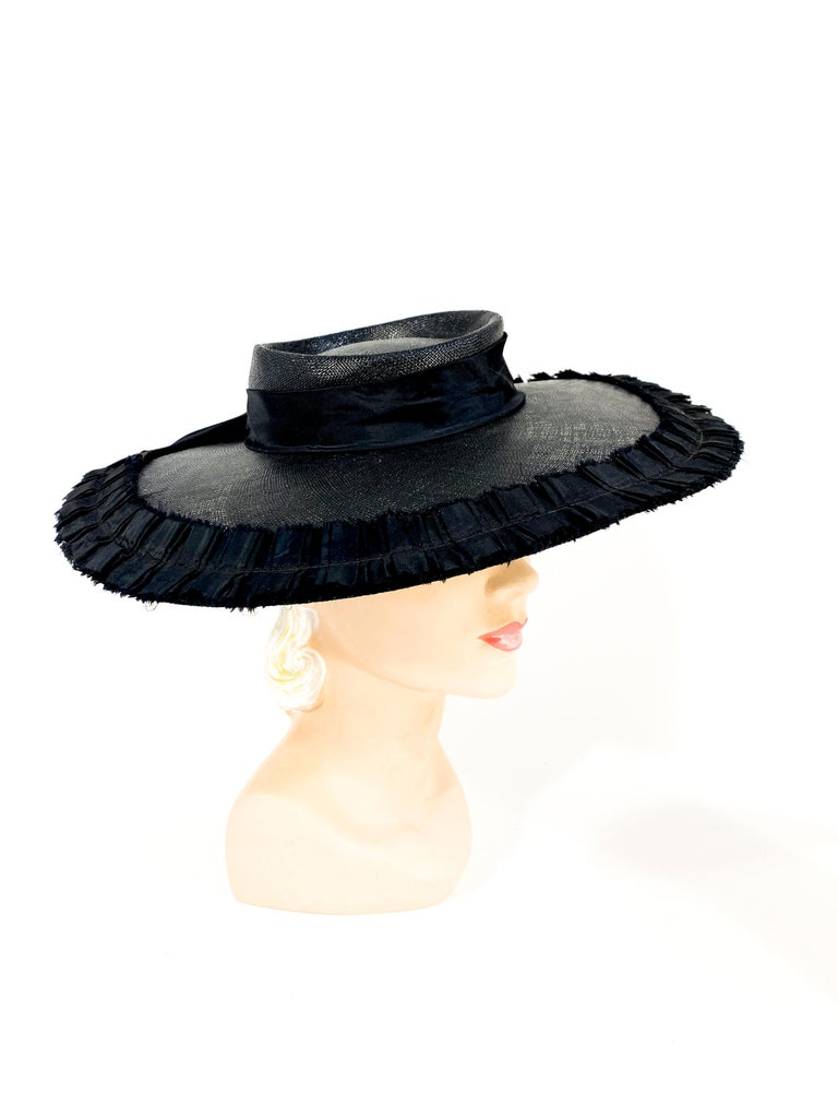 1940s black coated woven straw hat with a wide brim boarded with a black taffeta pleated trim. The shallow crown has a decorative black twill band. The wide grosgrain security band is attached to the interior of the hat and worn on the back of the