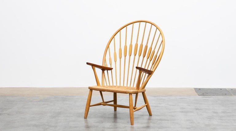 Peacock chair, ash, papercord by Hans Wegner, Denmark, 1974  Ashwood frames with teak armrests and original paper cord seat make the iconic peacock chair by Hans J. Wegner a work of art. What makes it special is the fusion of ergonomics and