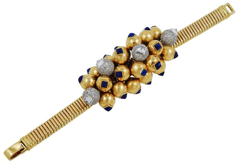 An opulent suite by Cartier consisting of a bracelet, ring, earrings, and a brooch each set in 18k yellow gold and adorned by several lapis lazuli throughout, with a pavé ball filled with round brilliant cut diamonds and a square-cut diamond at the