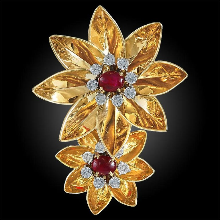 An exquisite piece by Cartier dating back to the 1940s, comprising a brooch designed as two flower heads made of 14k rose gold, each centering a cabochon ruby surrounded by a frame of brilliant diamonds. Signed Cartier