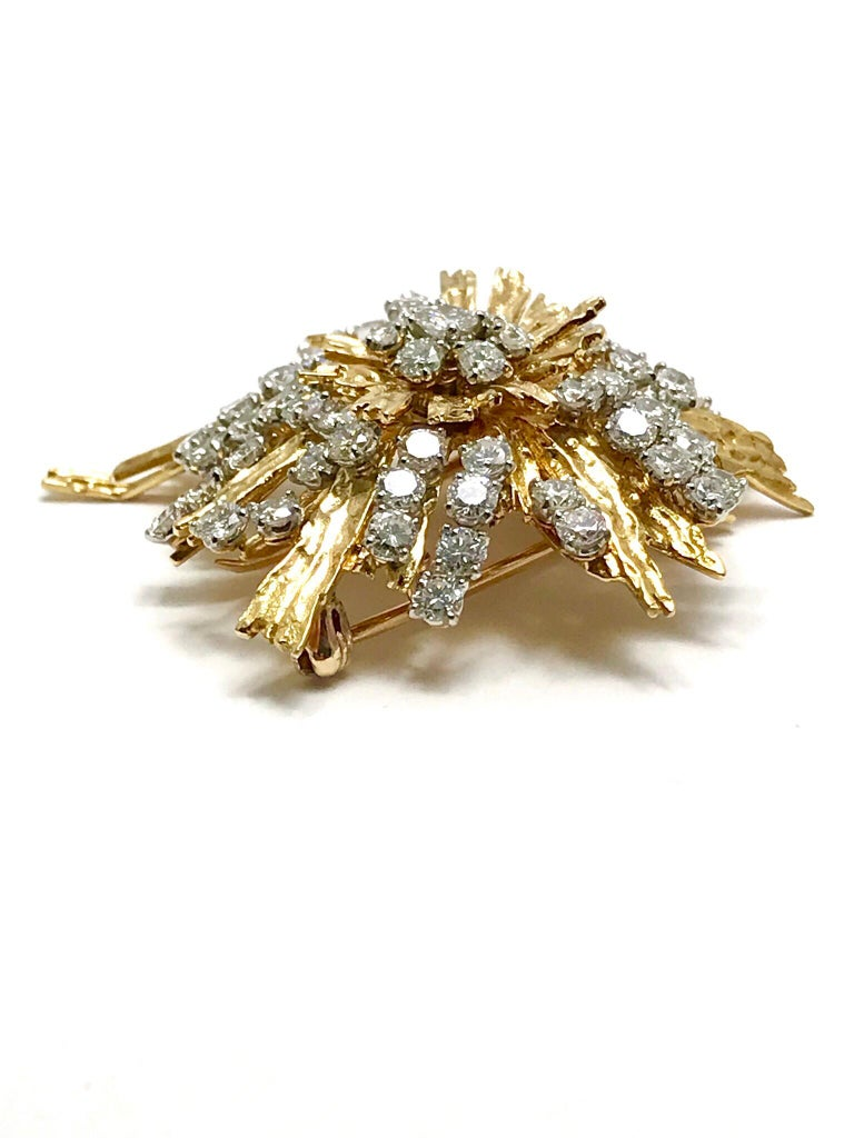 A stunning Cartier Paris Diamond Spray Brooch.  Emulating a firework exploding in the sky, the Diamonds are scattered about from the center in the 18 karat yellow textured gold.  The 61 round brilliant Diamonds have a total weight of 5.00 carats.