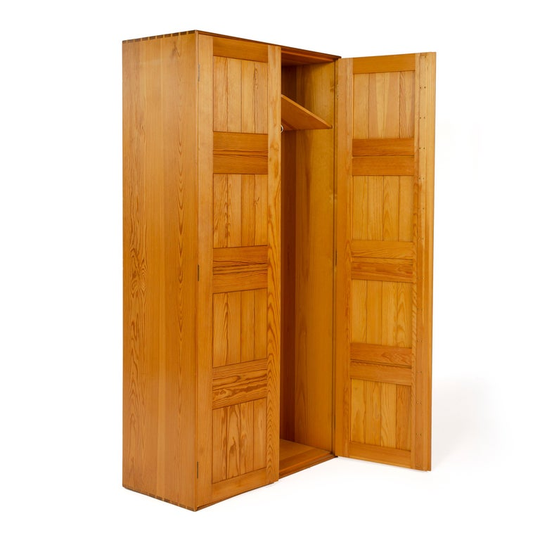 A two-door solid pine wardrobe with a dovetailed case and sliding brass hanger rod.