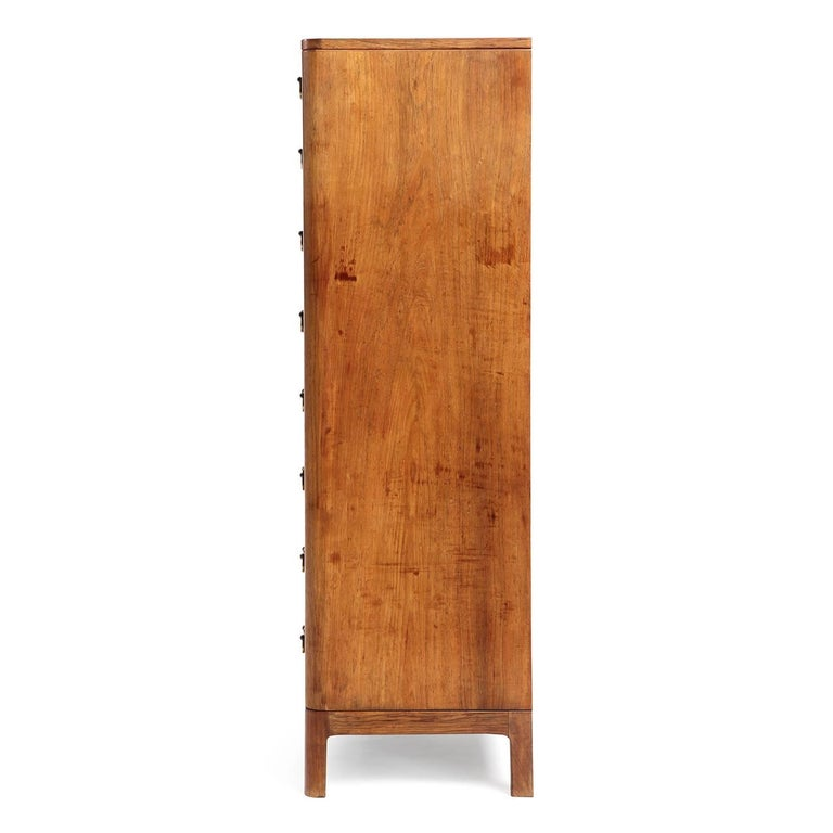 """An elegant and impeccably crafted tall chest of drawers in vividly figured rosewood having eight drawers with patinated brass """"handlebar"""" pulls."""