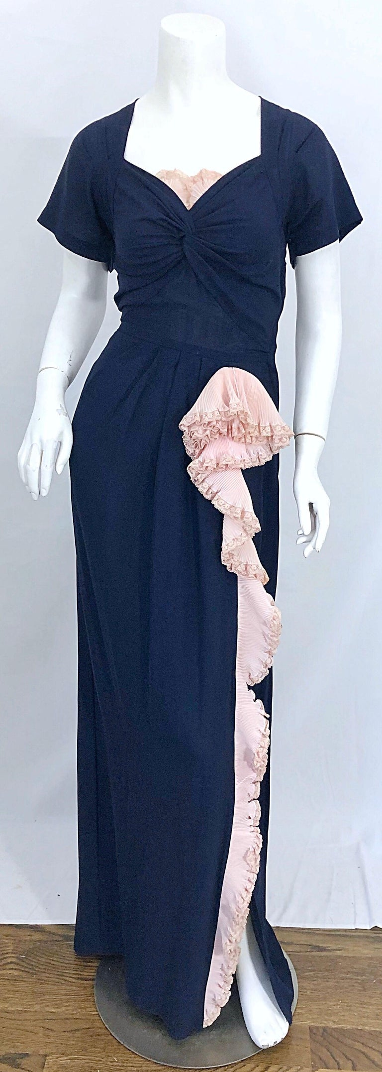 Beautiful vintage 1940s demi couture navy blue and light pink short sleeve crepe gown! Features a gathered sweetheart neckline with pale pink lace above the bust. Pale pink ruffle along the left leg, with a slight slit at the hem. The back of the